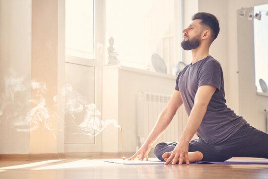 Serene young man doing pigeon pose in yoga studio