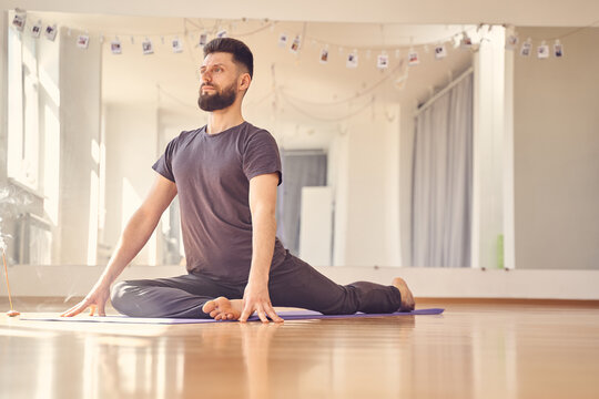 Athletic young man doing pigeon pose in yoga studio