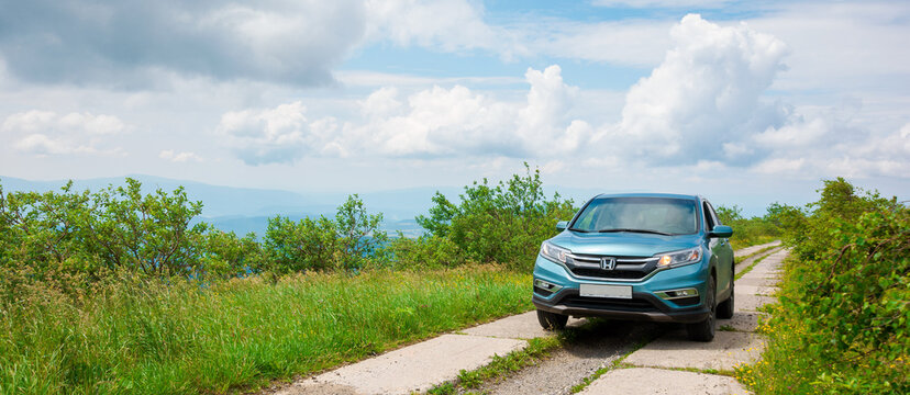 mnt. runa, ukraine - JUN 22, 2019: cyan honda cr-v suv on the mountain road. explore the wilderness concept. ridge in the distance. sunny weather. clouds on the blue sky