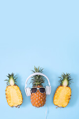 Funny pineapple wearing white headphone, concept of listening music, isolated on colored background...