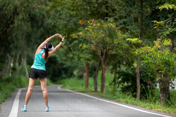 Healthy woman warming up before jogging run and relax stretching her arms and looking away in the road