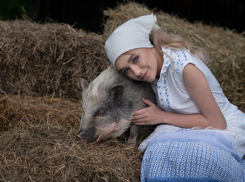 Art photo of a gentle village girl with a small spotted pig in the hayloft