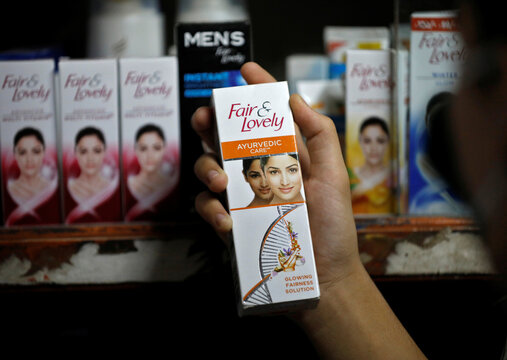 """A customer picks up """"Fair & Lovely"""" brand of skin lightening product from a shelf in a shop in Ahmedabad"""