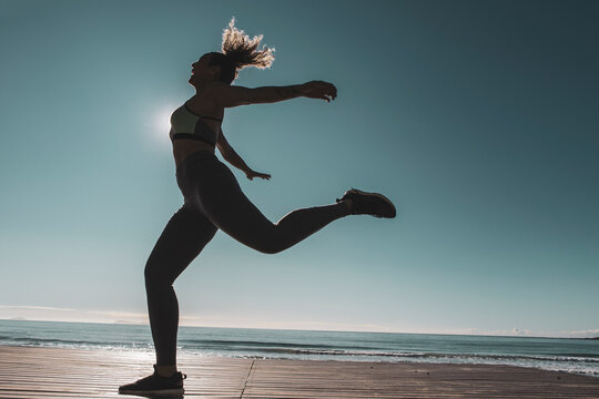 Young female dancer dances at sunset wearing sportswear . Silhouette backlight of the sun with body movements. Freedom and happiness concept.
