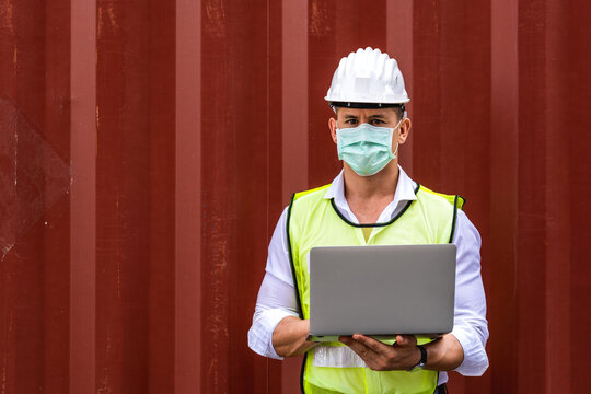 Worker man using a laptop waring surgical mask and safety white head to protect for pollution and virus in workplace during concern about covid pandemic