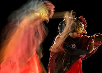 Javanese culture art dancer chicken mask in multi exposure shot with motion blur and dark background