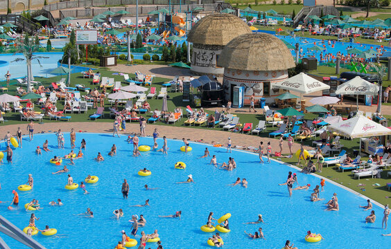 People cool down in water at the amusement park 'Dreamland' during a hot day in Minsk