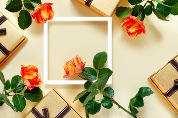 Beautiful yellow roses with golden gift box and white frame on delicate yellow paper background. ...
