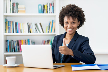 Happy african american business trainee working at computer