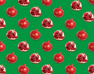 Fototapete - Pattern of whole and halved pomegranates on green background