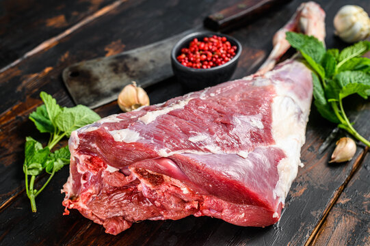 Whole raw leg of lamb. Fresh organic meat. Dark wooden background. Top view