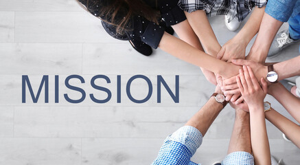 People holding hands together over light wooden background and text MISSION, top view