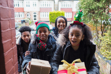 Portrait happy family delivering Christmas gifts at front stoop