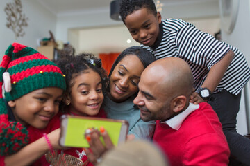 Happy family taking Christmas selfie with smart phone