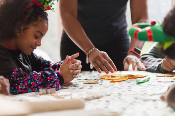 Girl decorating Christmas cookies with family at table