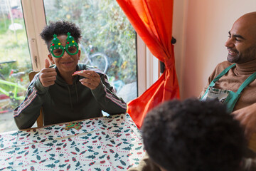 Portrait festive boy in Christmas glasses at table
