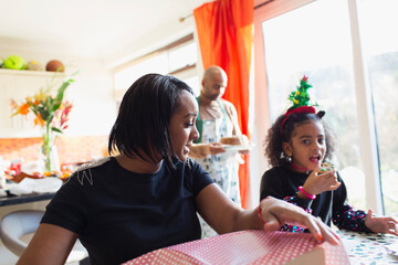 Mother and daughter wrapping Christmas gift and eating cookie at table