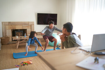 Father and daughter exercising in living room