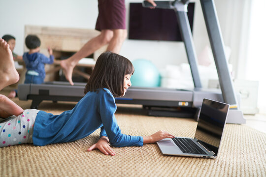 Girl using laptop in living room next to father on treadmill