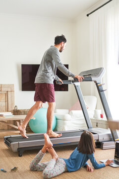 Daughter using laptop next to father on treadmill