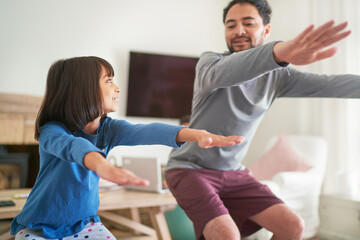 Father and daughter exercising doing squats in living room