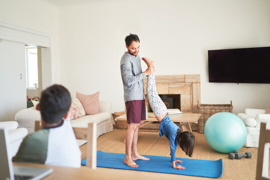 Father helping daughter to handstand on yoga mat in living room
