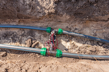 Water pipes (tubes) and control valves for irrigation system placed in a trench in the ground of a park
