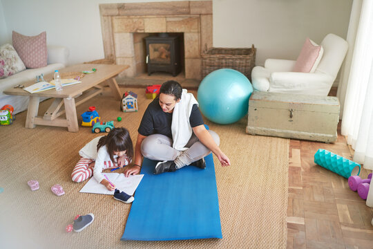Mother on yoga mat watching daughter coloring on living room floor