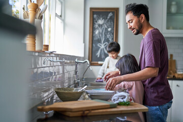 Father and kids doing dishes at kitchen sink