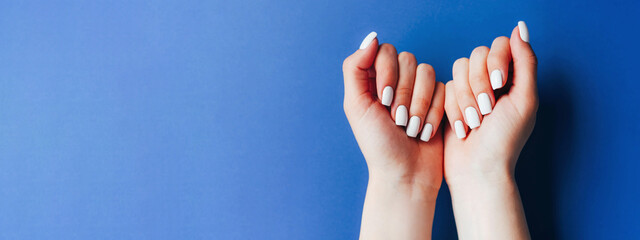 Banner with female hands and a white manicure on a blue background.