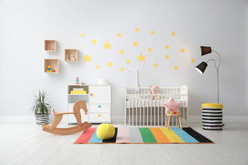 Stylish baby room interior with crib and toys