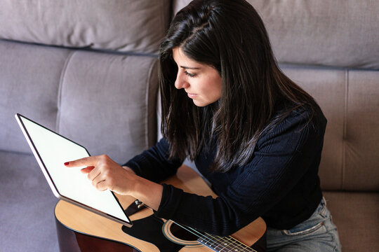 Woman playing guitar sitting on her couch at home and learning with online lessons with a digital tablet with a digital tablet with a blank screen from above