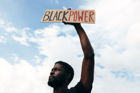"""Man protesting at a rally for racial equality holding a """"Black Power"""" poster. Black Lives Matter."""