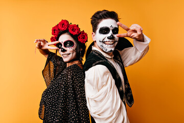 Laughing zombies standing on yellow background. Cute couple with mexican makeup chilling at...