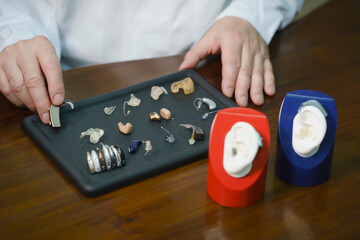 Midsection of audiologist various hearing aids at table in doctor's office