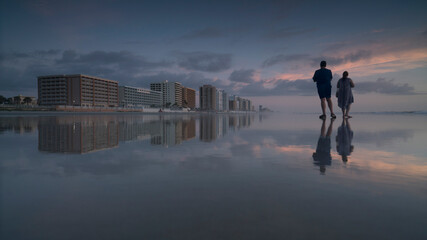 Young man and woman standing on shore at beach against sky during sunset, Daytona, Florida, USA