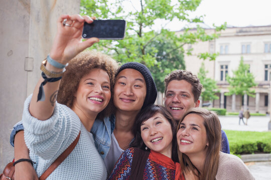 Smiling young woman taking selfie with multi-ethnic friends, Berlin, Germany