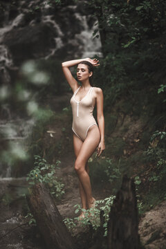 Woman in swimsuit standing in forest