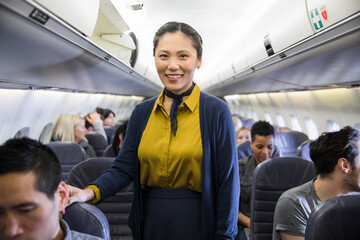 Portrait confident female flight attendant in airplane aisle
