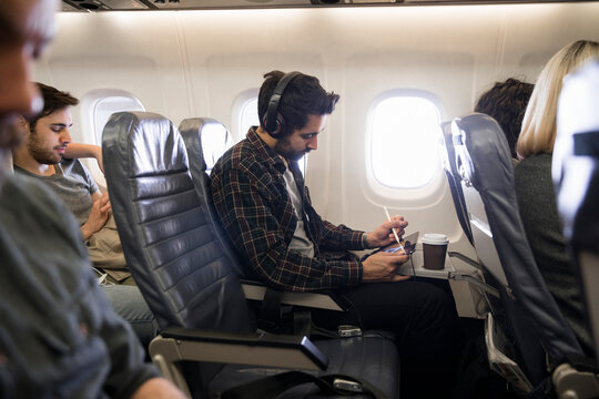 Man using digital tablet and stylus on airplane