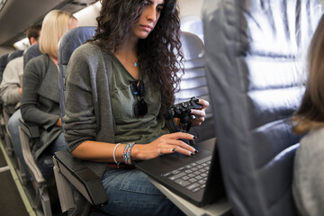 Woman with camera and laptop working on airplane