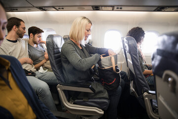 Senior woman looking in purse in airplane