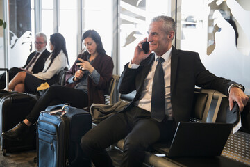 Businessman talking on smart phone in airport departure area