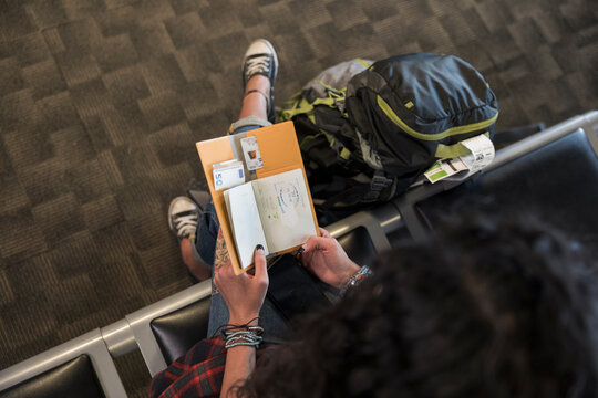 Woman looking at passport in airport departure area