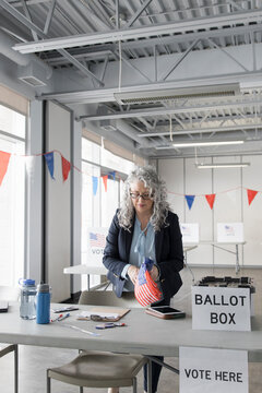 Woman holding American flags on voting day at polling place