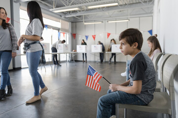 Boy with American flag waiting in polling place