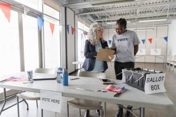 Female volunteers with clipboard preparing in American polling place