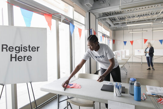 Volunteer arranging American flags at polling place