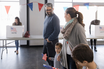 Happy family with American flags leaving polling place