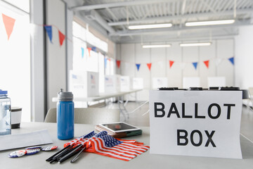 Ballot box and American flags on table in polling place